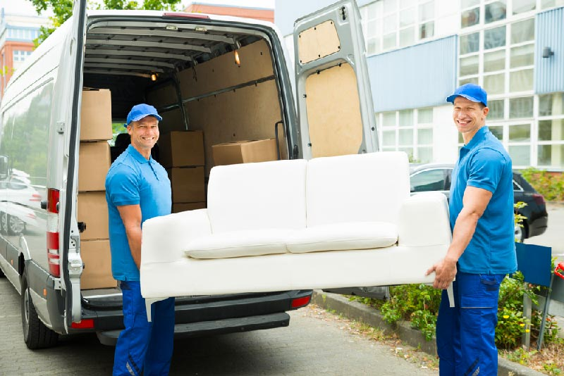 two moving men moving couch from truck into home