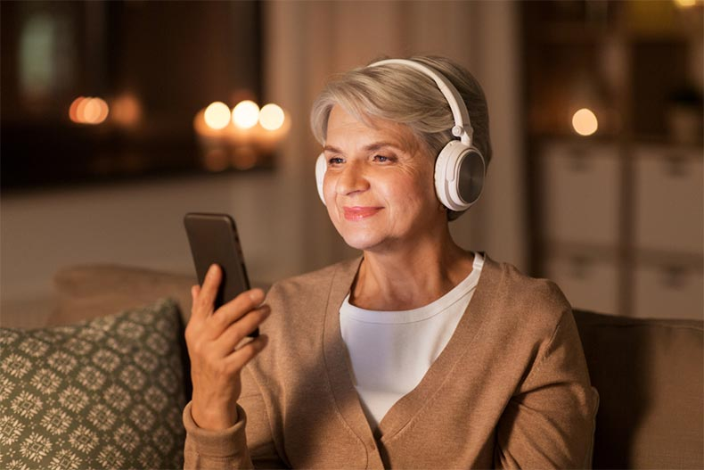 A senior woman wearing headphones and smiling while listening to music on a smartphone at home in the evening