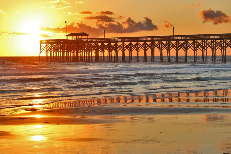 A golden sunrise over a wooden pier along the beach in Myrtle Beach, South Carolina