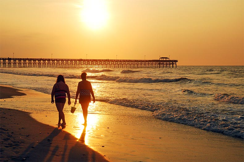 Two women walking on the shores of Myrtle Beach during a stunning, orange sunset