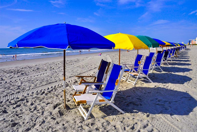 View of lawn chairs and beach umbrellas lined along a shore in Coastal South Carolina
