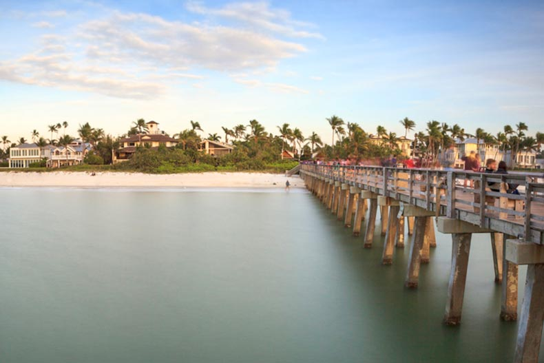 View of the Naples Pier and the shoreline at sunset in Naples, Florida