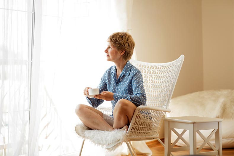 An active adult woman sitting on an armchair and looking out a window while drinking tea.