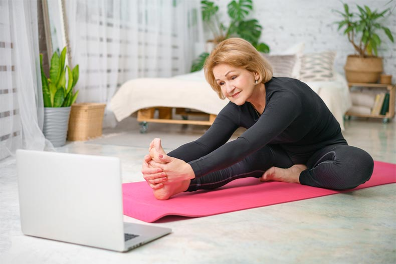 An active adult woman doing yoga at home with her laptop