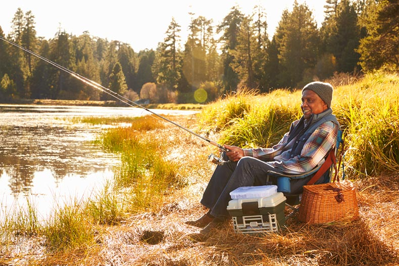 A senior man sitting by a riverside and fishing on an autumn day