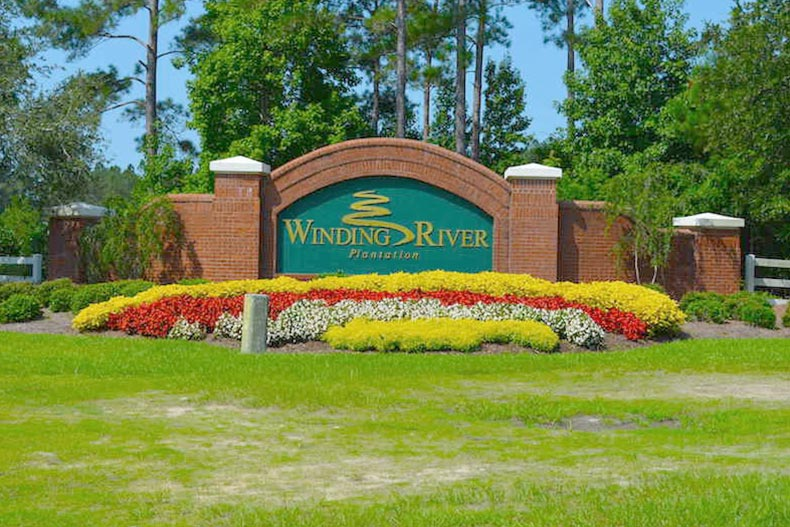 Flowers blooming around the community sign for Winding River Plantation in Bolivia, North Carolina