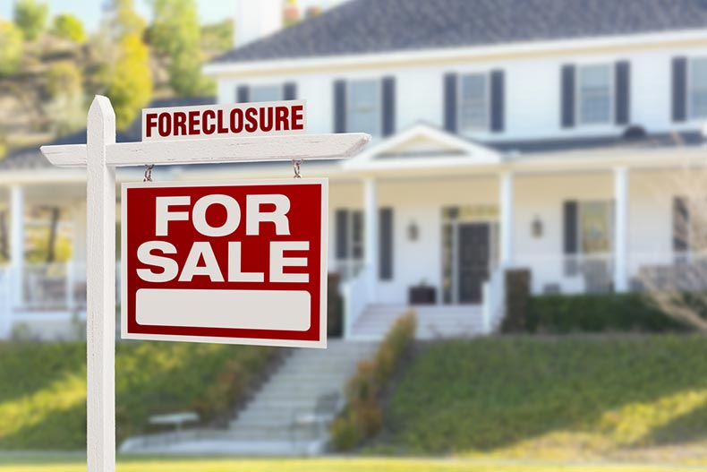 "A foreclosure ""Home For Sale"" sign in front of a large house"