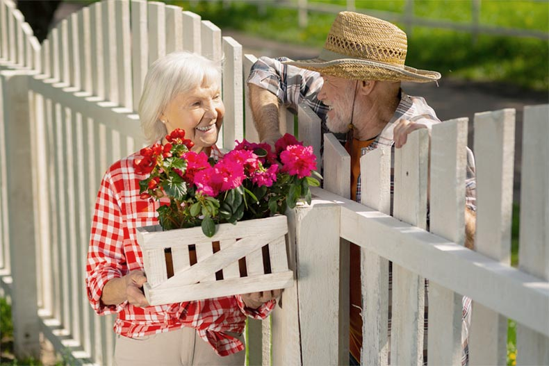 An older woman with flowers talking to an older man over a fence
