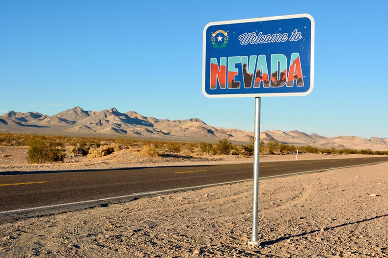"A ""Welcome to Nevada"" road sign along a highway"