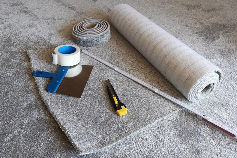 Tools on top of a roll of new carpet