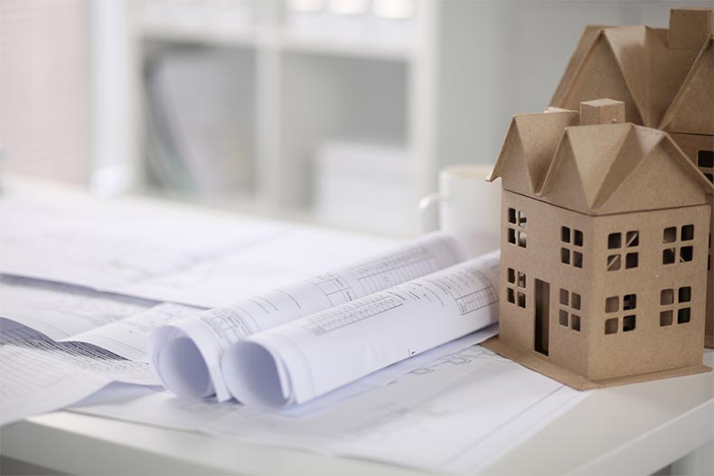 Blueprints for a new construction home rolled up beside a paper model of a house