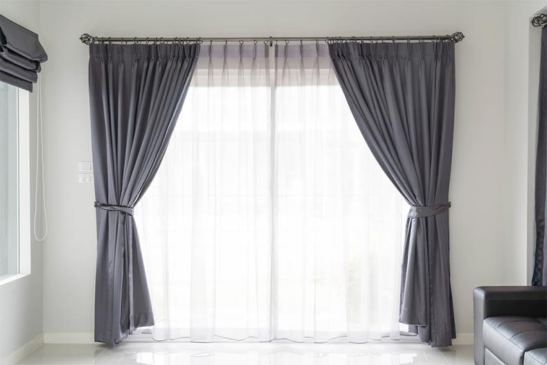 Gray curtains framing a large window in a living room