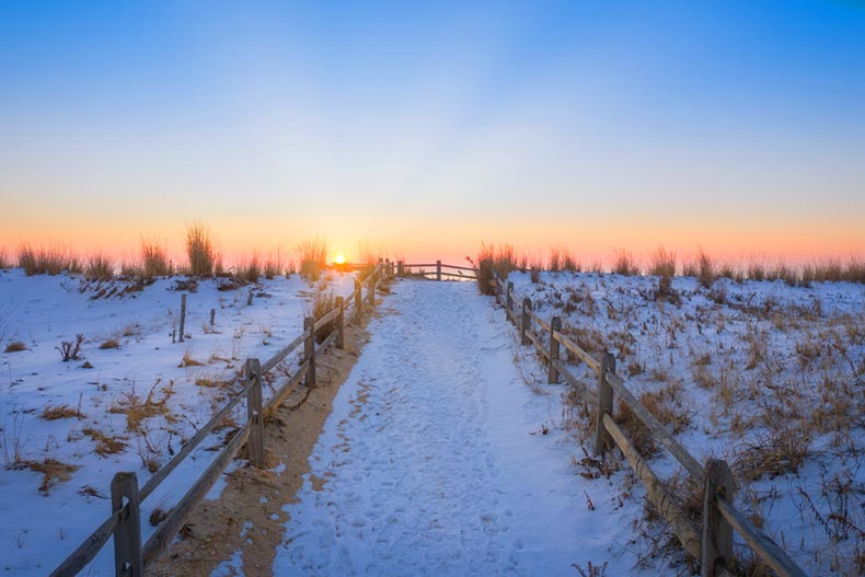 Sunrise over a snowy pathway leading to the beach in New Jersey