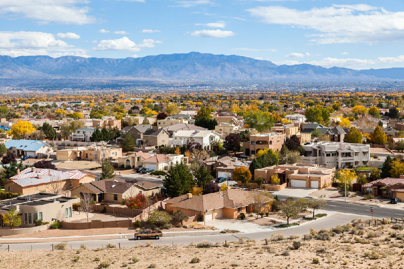aerial of new mexico neighborhood homes with mountain range and blue sky