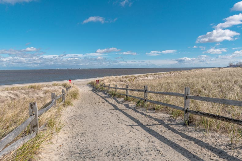A blue sky over a wooden fence leading to the shoreline at Bayshore Waterfront Park in Monmouth County, New Jersey
