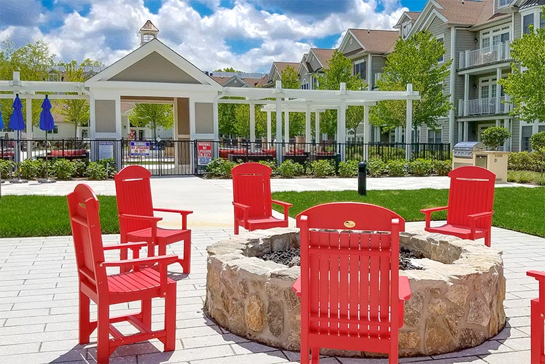 Wooden chairs surrounding the outdoor fire pit at Nobility Crest at Ocean in Ocean Township, New Jersey