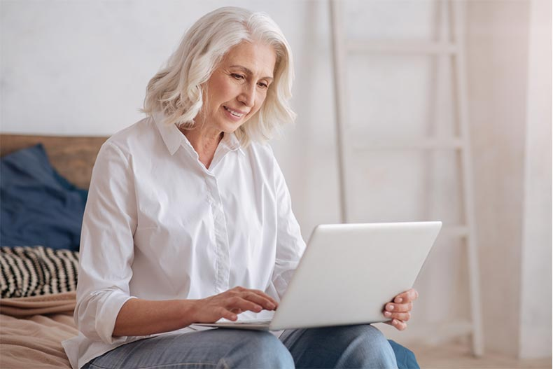 An older woman browsing listing photos on her laptop