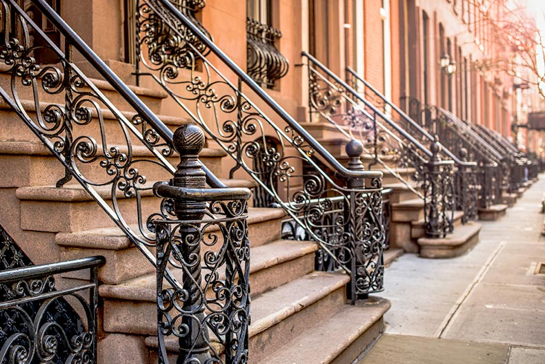 View of wrought iron railings outside brownstone apartment buildings in New York City