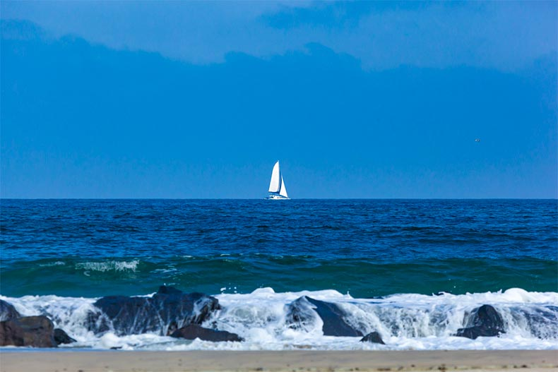 Sailboat off the shore of Ocean County, NJ under a blue sky