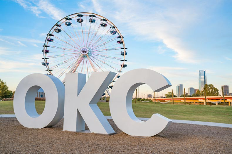 The OKC sign and ferris wheel with the Oklahoma City skyline in the background