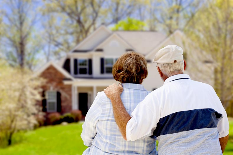 Active adult couple from behind looking at a house