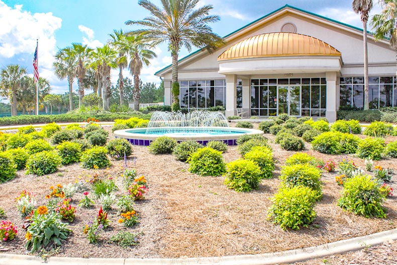 Exterior view of groomed landscaping, a flagpole, and palm trees outside the clubhouse at On Top of the World in Ocala, Florida