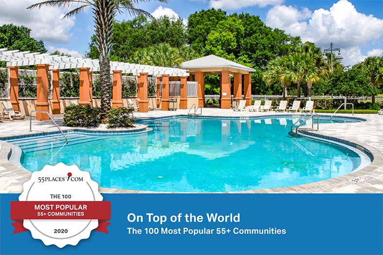 An outdoor pool with a patio, palm trees, and cabanas at On Top of the World in Ocala, Florida with an award badge and banner at the bottom