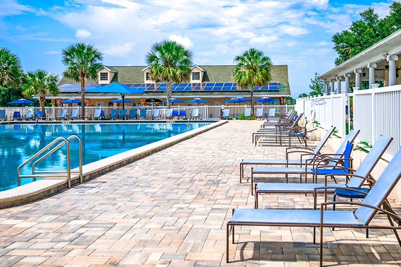 Lounge chairs on the patio beside an outdoor pool at On Top of the World in Ocala, Florida