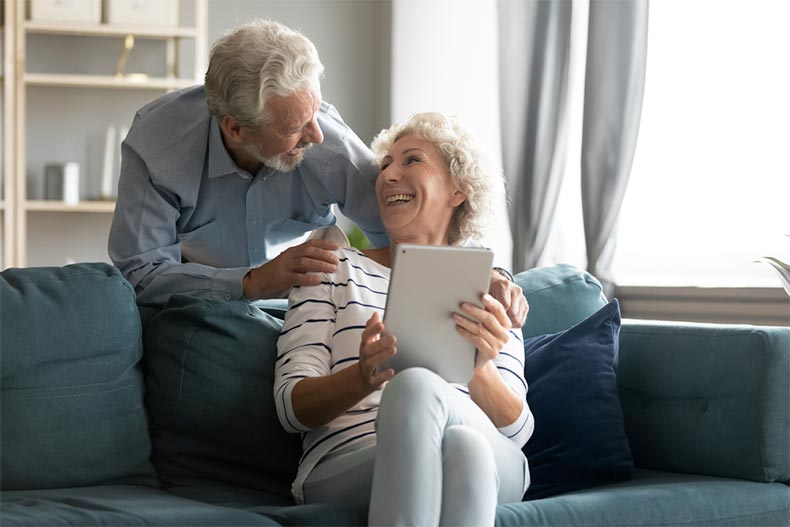 An excited older man and woman having fun with a computer tablet