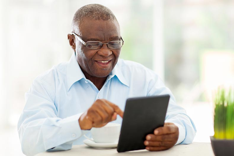 A cheerful senior man enjoying an online hobby on a tablet at home