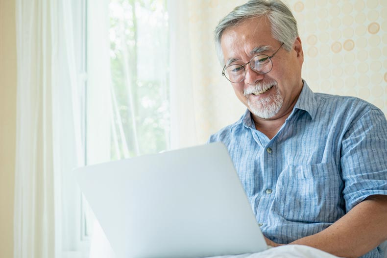 A happy senior man using his laptop to explore new interests and hobbies