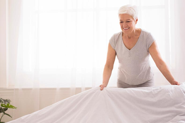 A senior woman making a bed and organizing a room in the morning