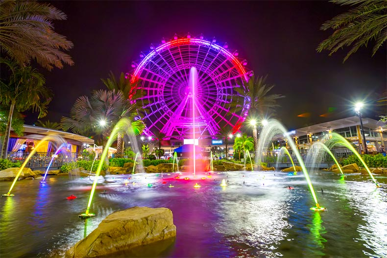 The wheel in Orlando, FL lit up at night with lighted fountain in foreground
