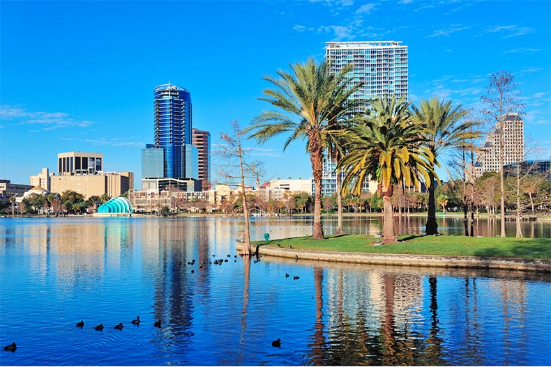 Lake Eola on a blue day with palm trees and downtown Orlando in the background