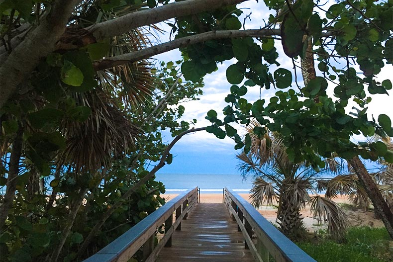 Canopy over a wooden walking bath leading onto a beach