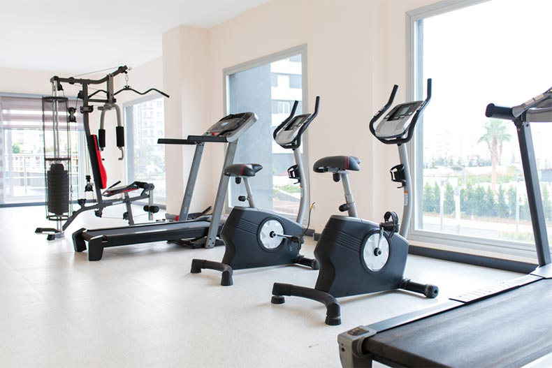 Interior view of an exercise room with cardio and weight-lifting equipment