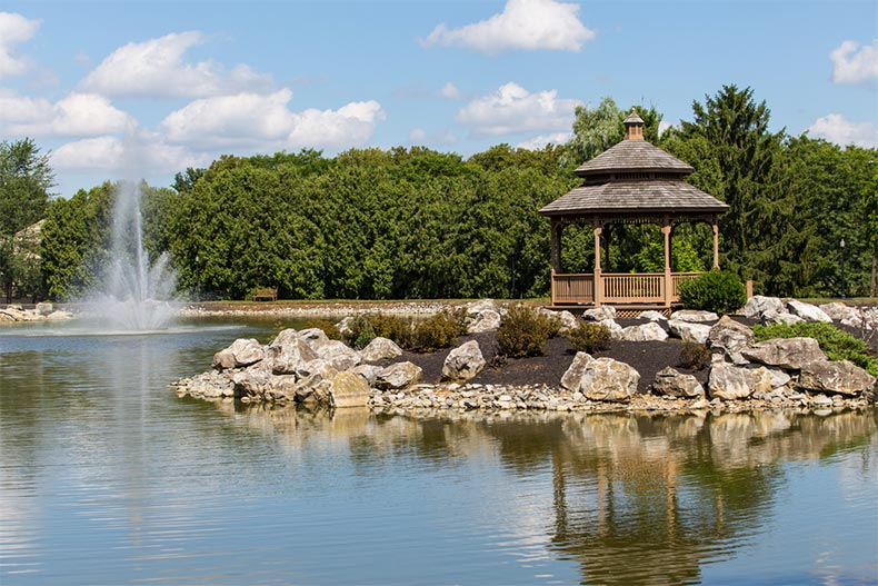 A blue sky over a fountain and a gazebo at a pond in a public park near Lancaster, Pennsylvania