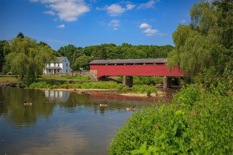 A red covered bridge stretching across a pond in South Whitehall Township in Allentown, Pennsylvania