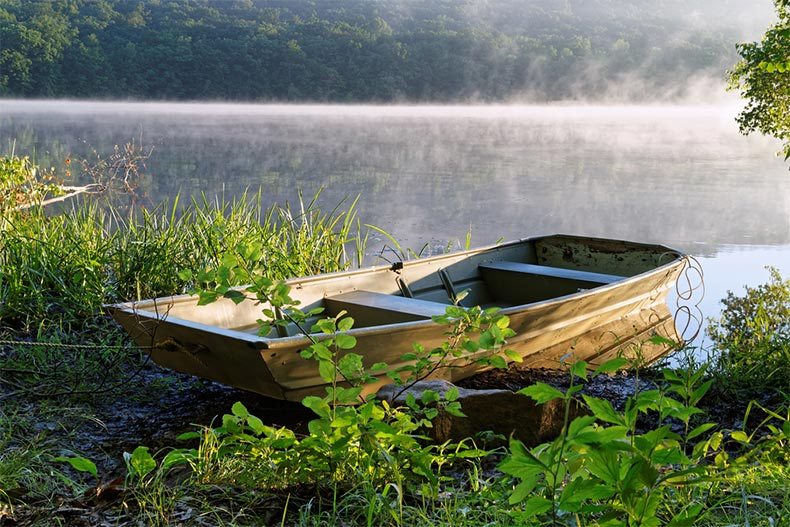 A fishing boat tied at the shore of a Pennsylvania lake with the morning sunlight shinning on the fog