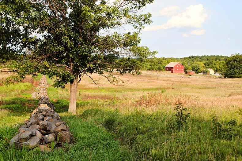 A stone wall, trees, and a red barn in Gettysburg National Military Park in Pennsylvania