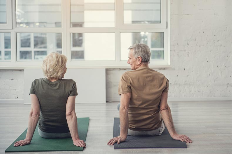 Older man and woman sitting on yoga mats with their back to camera