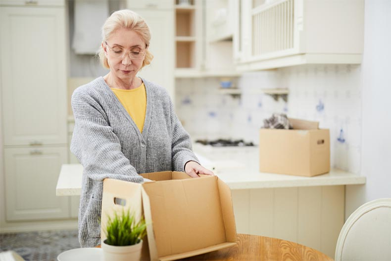 An older woman packing items into a moving box