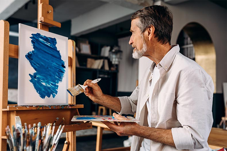 A male artist sitting in front of easel and painting an abstract picture with a large paintbrush