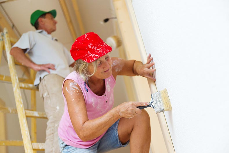 An active senior couple painting a wall in their new house