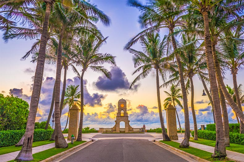 Palm tree-lined walking path onto shores of Palm Beach. Monument in the middle of the photo opens up to scenic horizon