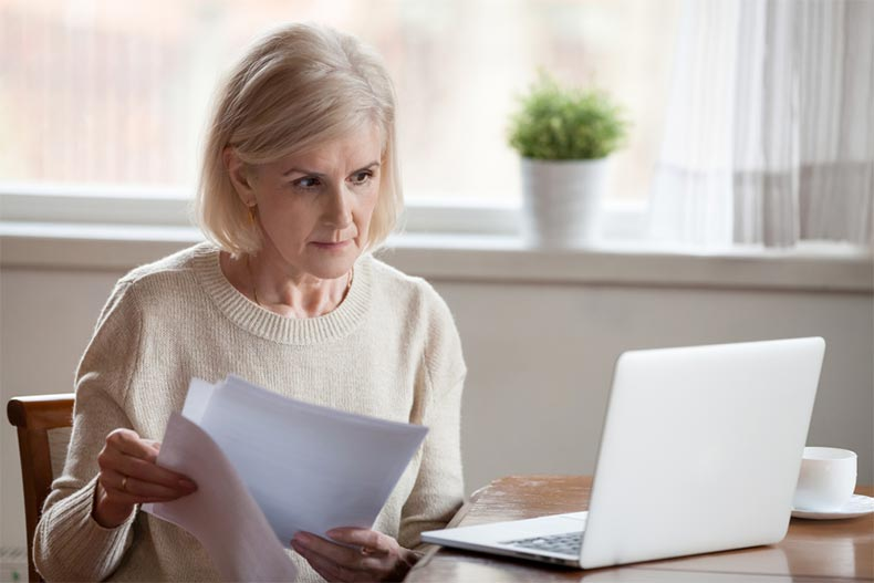 An active adult woman looking at her laptop while going through homebuying paperwork
