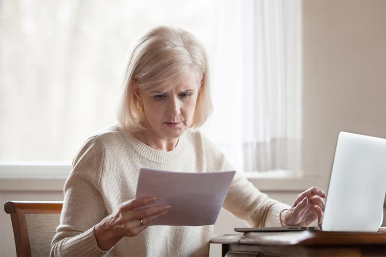 A senior woman looking over some paperwork with a serious expression