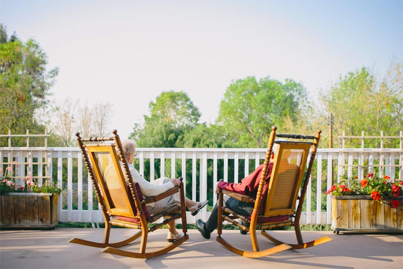 peaceful backyard setting with two active adults sitting in rocking chairs on a deck