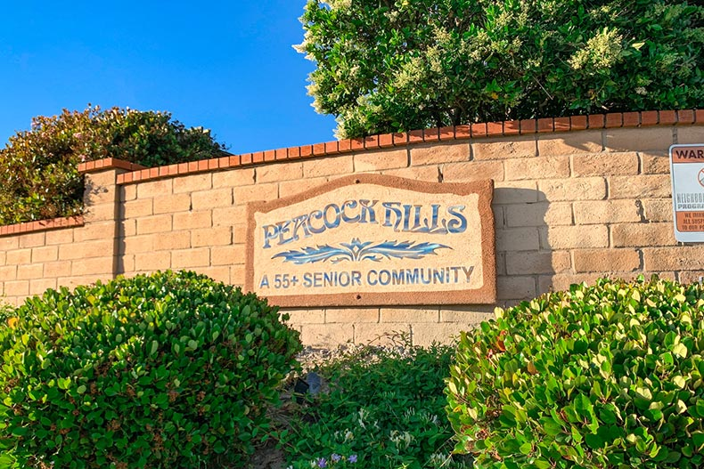 Greenery and a brick wall surrounding the community sign for Peacock Hills in Oceanside, California