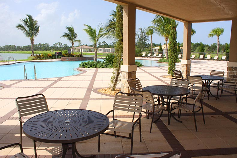 Tables and chairs on the patio beside the outdoor pool at PGA Village Verano in Port St Lucie, Florida